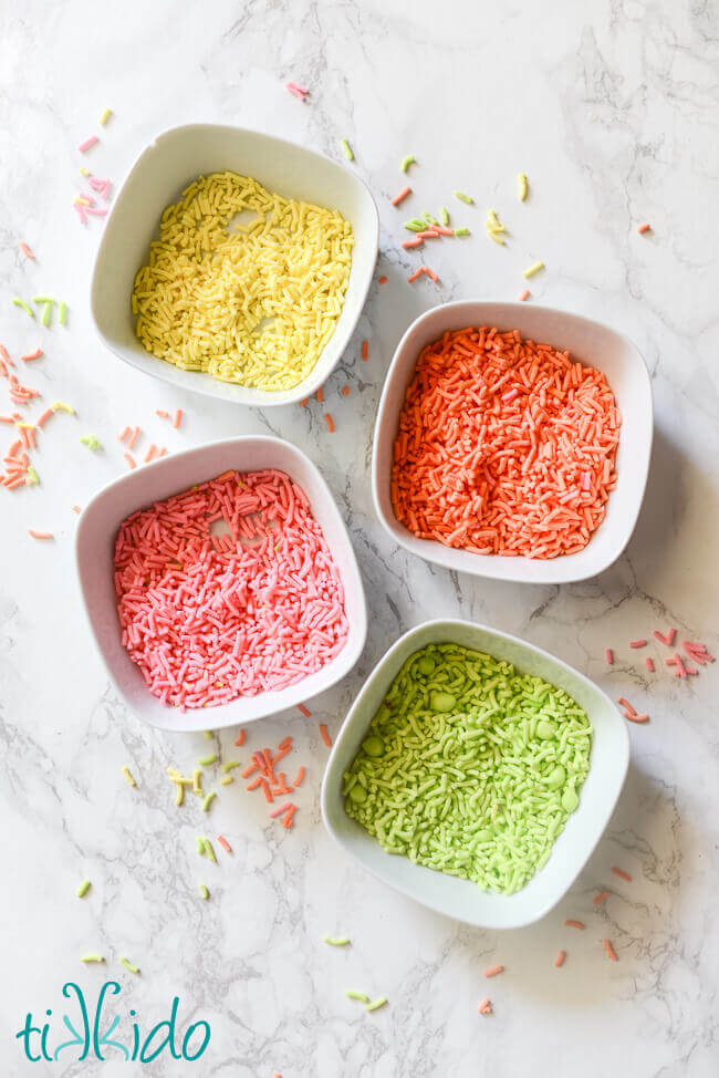 Homemade sprinkles in white bowls on a white marble background.