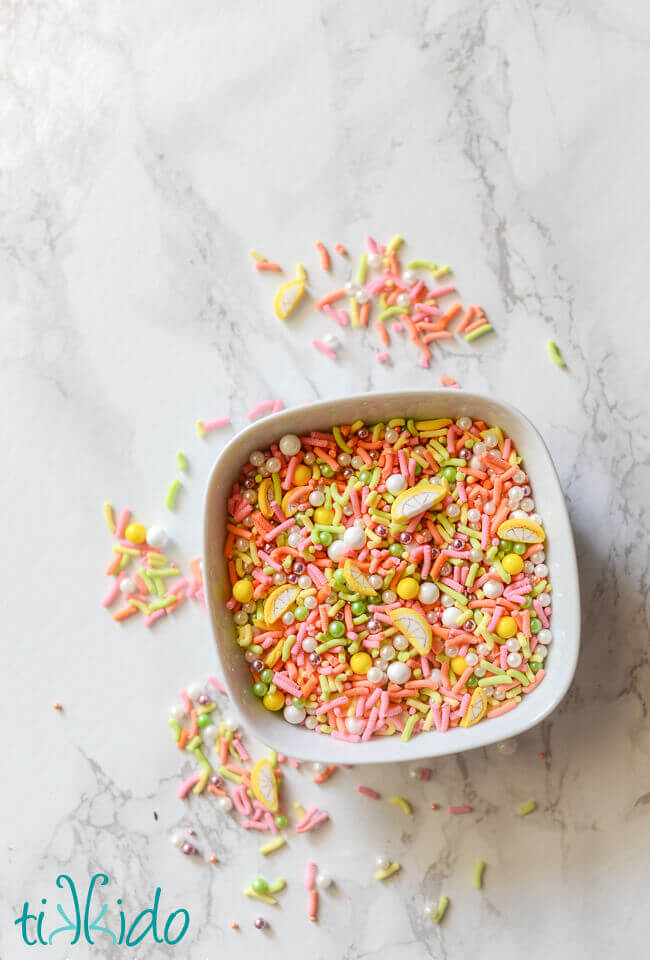 Homemade sprinkles mixed together in a white bowl on a white marble background.