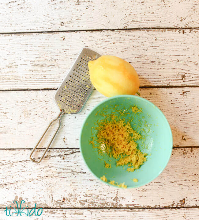 Zested lemon and microplane zester on a white wooden surface, next to turquoise bowl of lemon zest.
