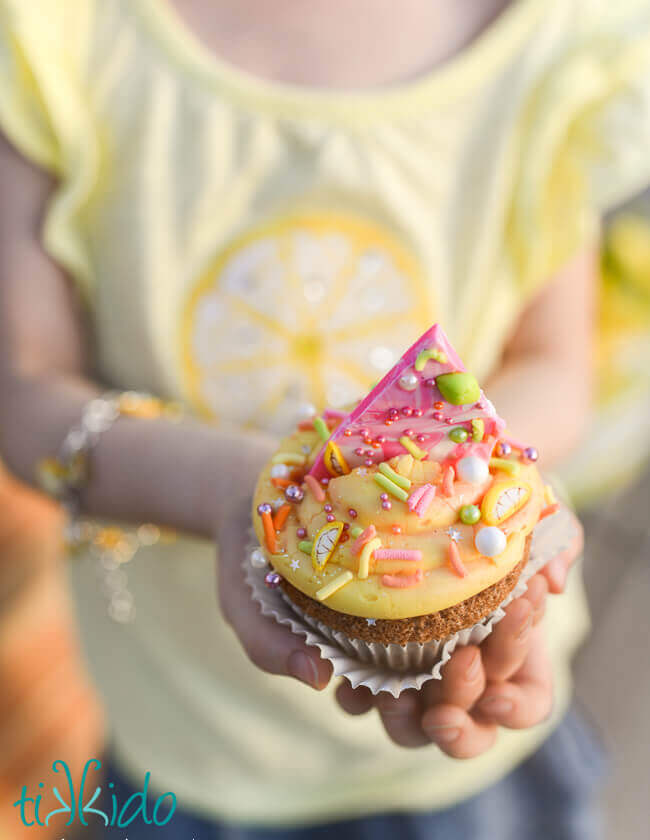 Homemade sprinkles on a cupcake being held by a little girl.