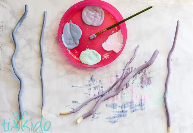 Pieces of curly willow being painted in pastel colors, a pink plastic plate with paint and a paintbrush in the center.