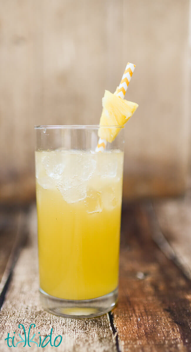 Pineapple and coconut rum summer cocktail in a tall glass, with a yellow and white chevron striped paper straw and a chunk of fresh pineapple.