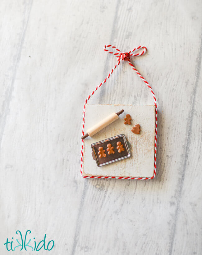 Christmas ornament that looks like a miniature baking scene with a tiny pan, rolling pin, and gingerbread cookies.