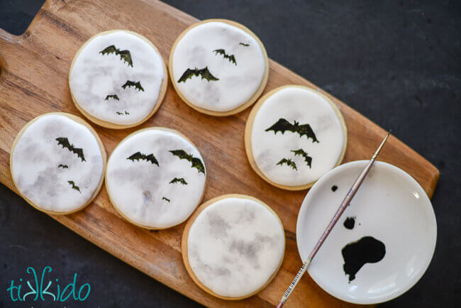 Painting bat silhouettes on the full moon decorated sugar cookies.