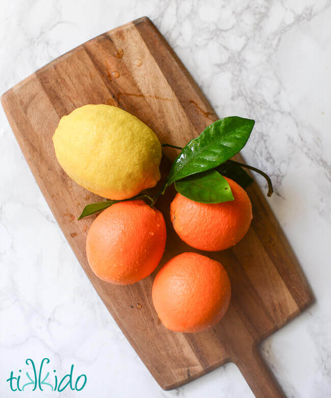 Fresh oranges and a lemon on a wooden cutting board.