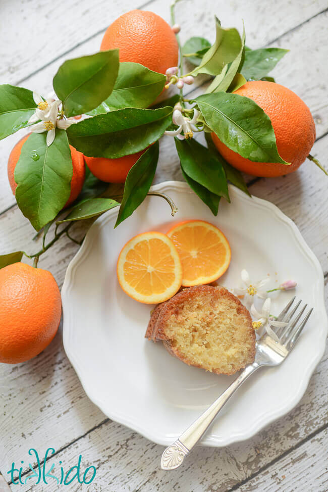 Amazingly flavorful orange bundt cake slice on a white plate surrounded by oranges, orange tree branches, and orange blossoms.
