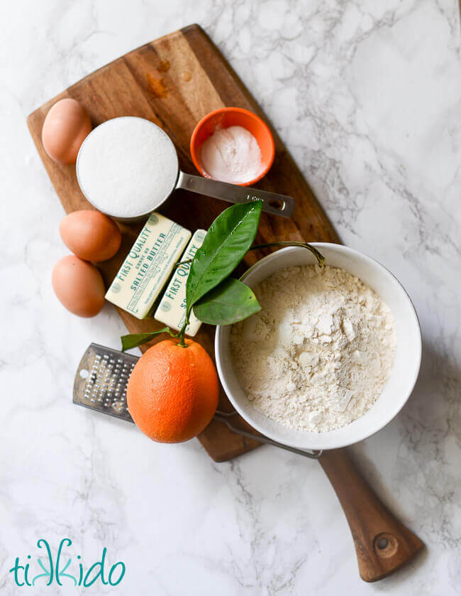 Ingredients for the BEST orange bundt cake on a wooden cutting board.