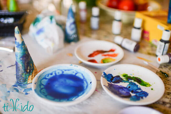 Three small white plates with food coloring paints, bottles of food coloring, and ice cream cones in the process of being painted.
