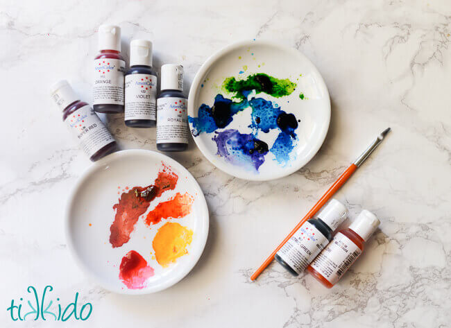 Collection of gel food colorings and two small white plates used as paint palettes