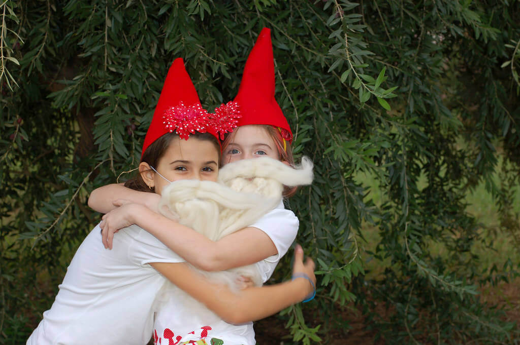 two little girls hugging and wearing gnome hats and gnome beards