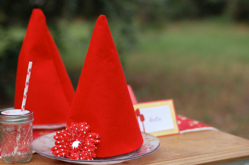 Two gnome hats with red and white polka dot flowers sitting on a table. 47770fd472b