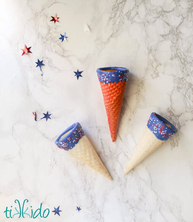 Red, white, and blue ice cream cones with chocolate and sprinkles.