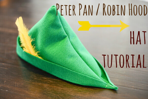 Green Felt Peter Pan Hat With A Yellow Feather Tucked In The Brim On
