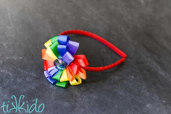 Rainbow DIY headband made with satin ribbon on a black chalkboard background.