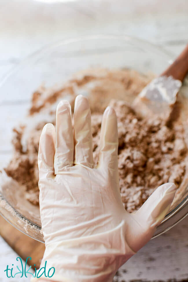 Hand wearing a plastic food service glove to make gingerbread salt dough ornament recipe.