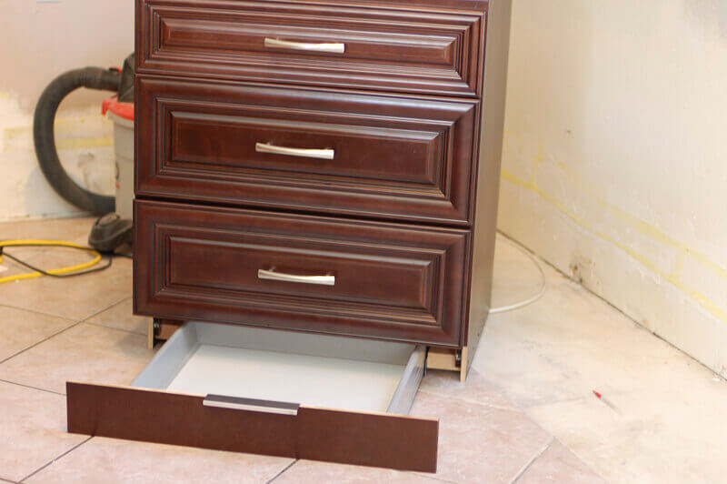 Kitchen cabinets with hidden toe kick drawer