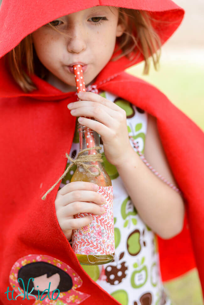 Little girl in a red riding hood cape drinking Sparkling Apple Cider