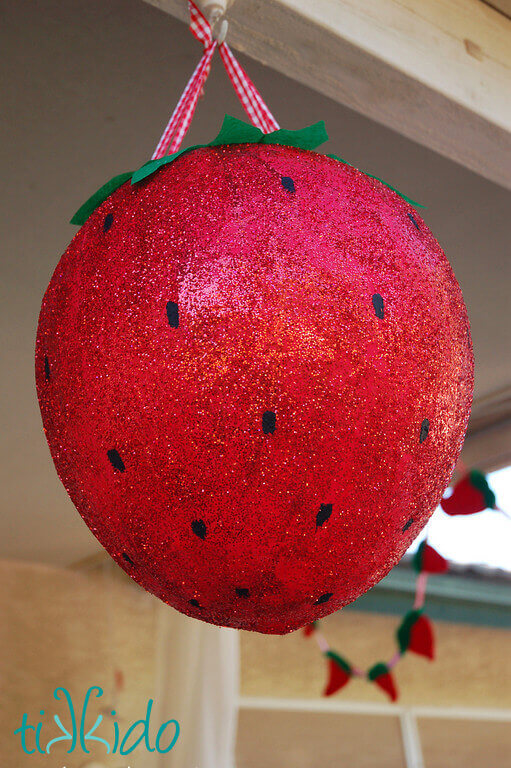 Pinata that looks like a giant, glitter covered strawberry at the Strawberry Picnic birthday.