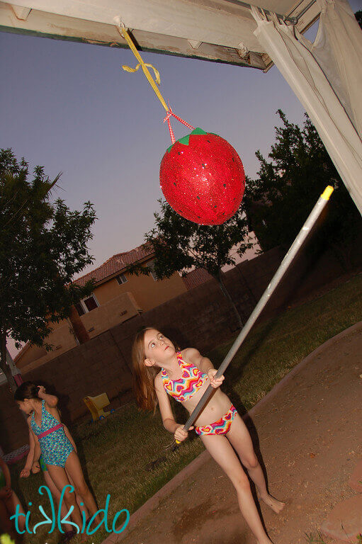 Little girl swinging at the strawberry piñata at the Strawberry Picnic birthday.