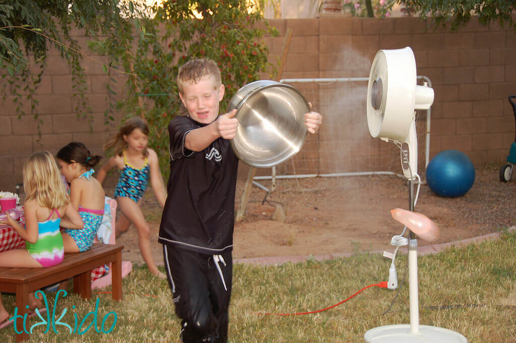 Little boy throwing a water balloon from a silver bowl.