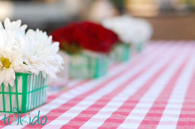 Red and white flower arrangements in green plastic strawberry baskets at the Strawberry Picnic birthday.