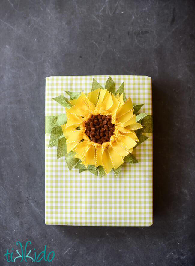 DIY ribbon sunflower gift topper on a green gingham check wrapped gift.
