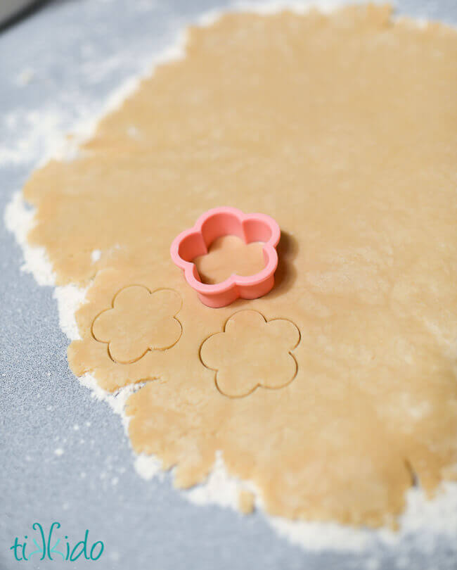Sugar cookie dough rolled out, being cut into flower shapes with a small pink flower cookie cutter.