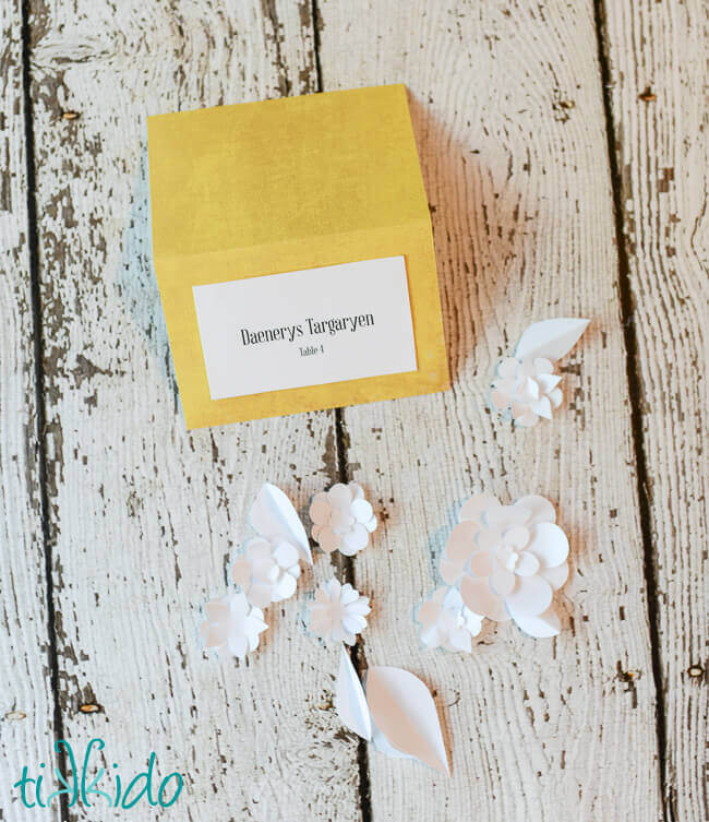 miniature paper floewrs made from white paper next to a plain wedding seating card.