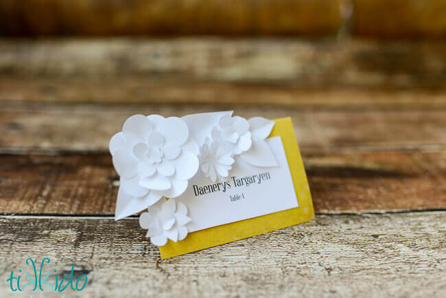 DIY seating card embellished with miniature white paper flowers