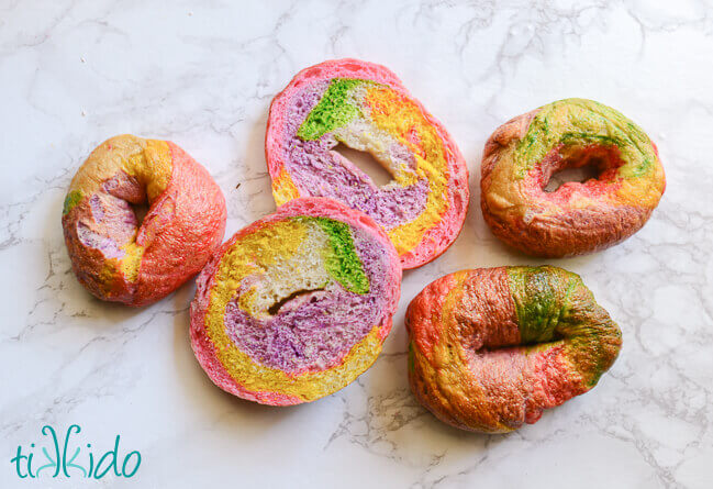 One unicorn bagel cut in half, surrounded by three whole unicorn bagels on a white marble background.