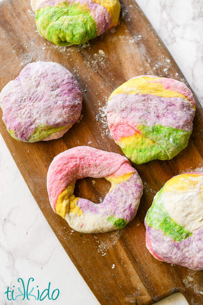 Unicorn bagel dough being shaped into bagel shapes.