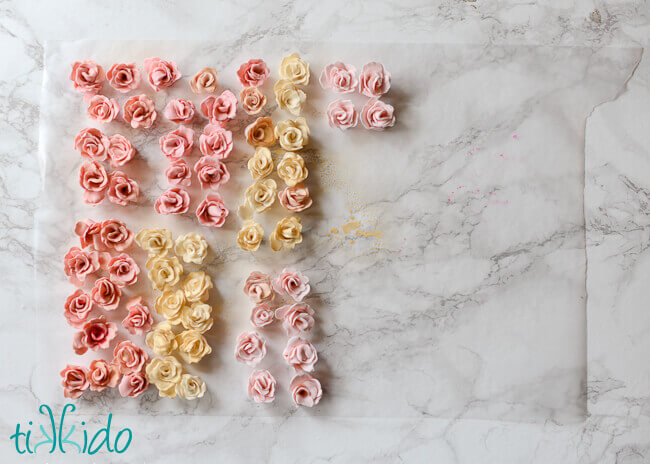 Collection of pink and white gum paste roses drying on waxed paper on a white marble background.