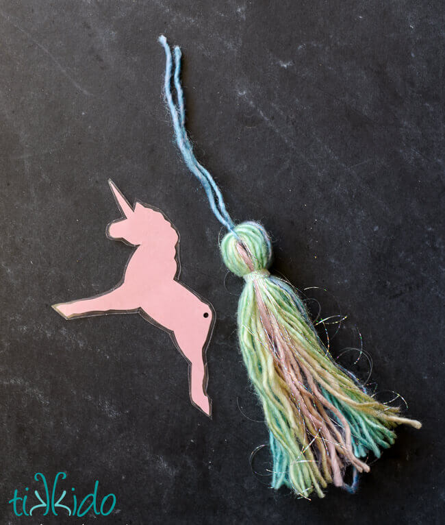 DIY unicorn bookmark with yarn tassel tail being assembled on a black chalkboard background.