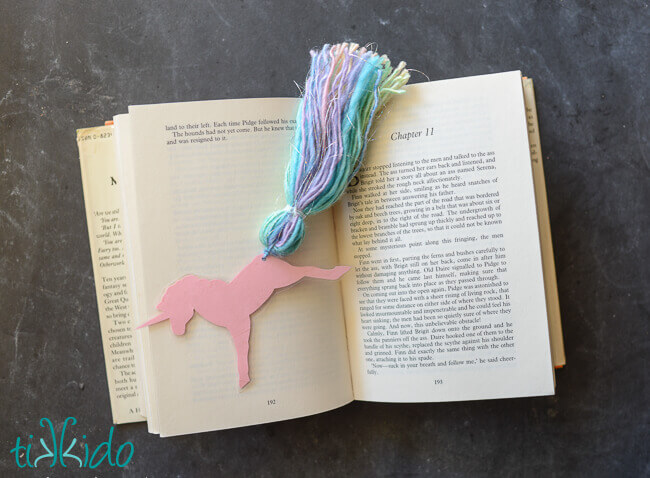 Unicorn bookmark with a yarn tassel tail on an open book.