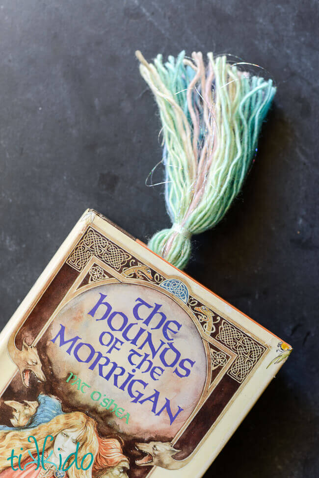 Yarn tassel tail of a unicorn bookmark sticking out of the top of The Hounds of the Morrigan book.