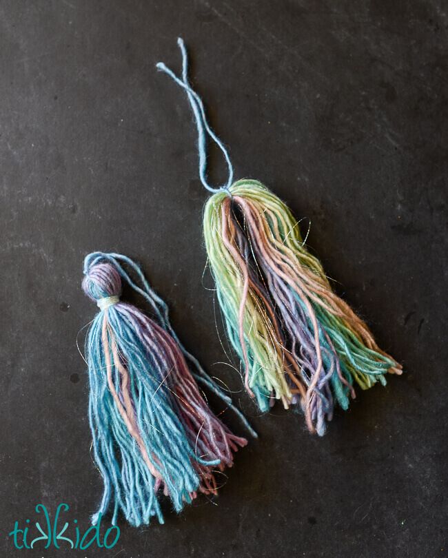 Two yarn tassels made with pastel rainbow yarn being tied into tassel shapes.