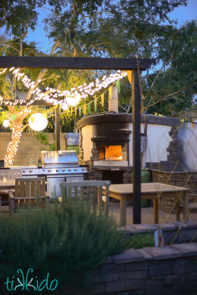 Wood fired pizza oven with a fire inside, framed by an outdoor kitchen and eating area, and covered with a pergola strung with twinkle lights and paper lanterns.