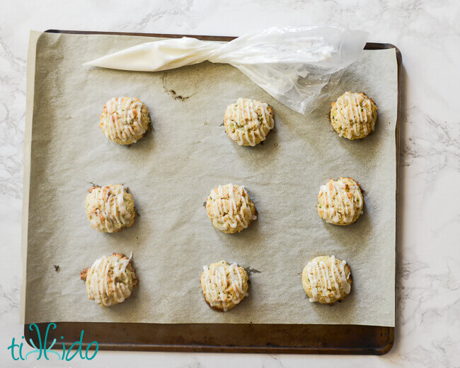 Baked soft zucchini cookies being drizzled with lemon glaze.